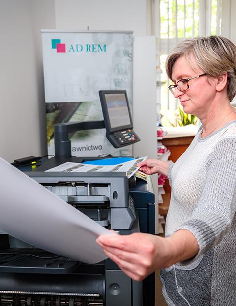 kobieta obsługująca maszyne drukarską - Wydawnictwo Ad Rem
