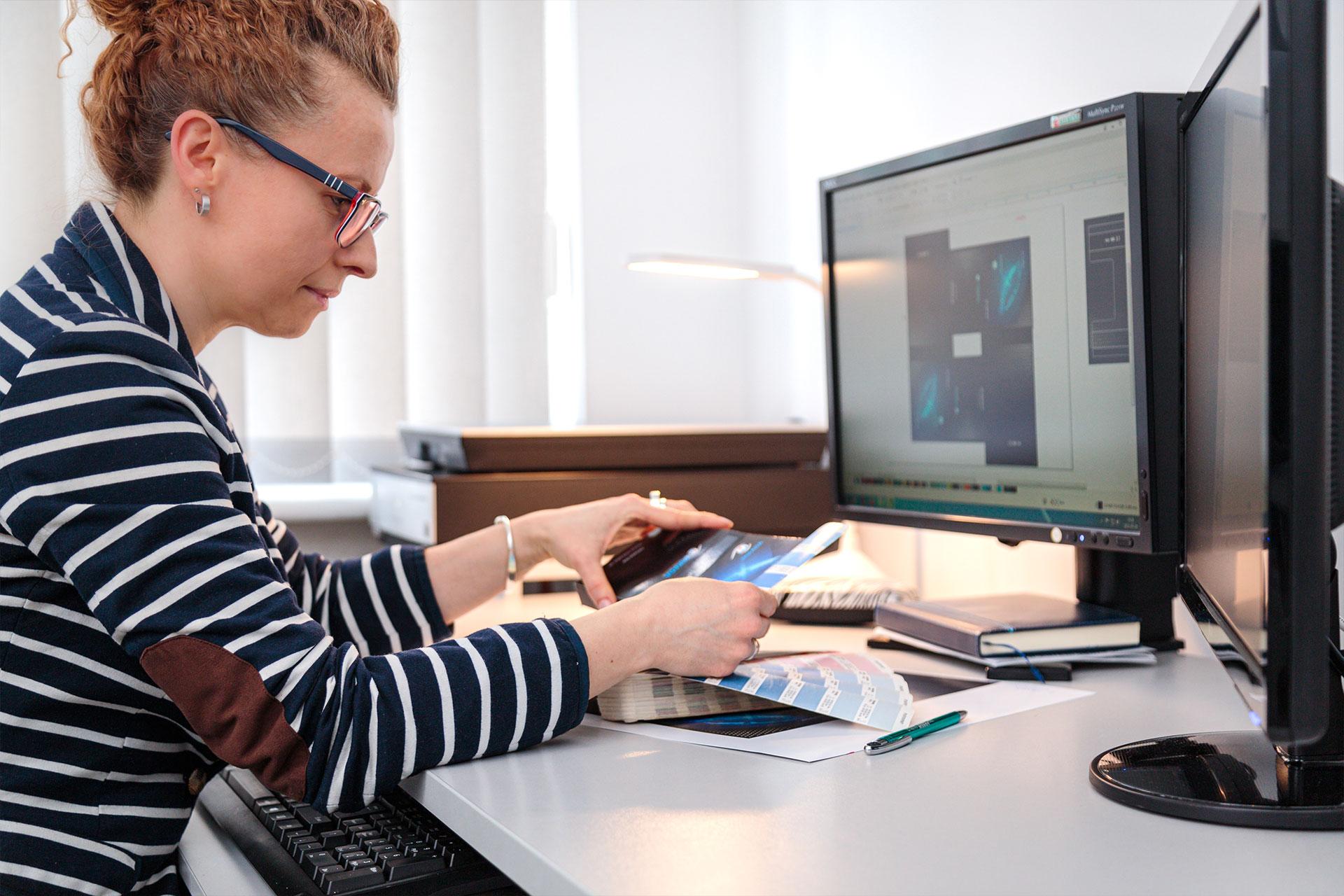 kobieta przy komputerze przygotowująca druk