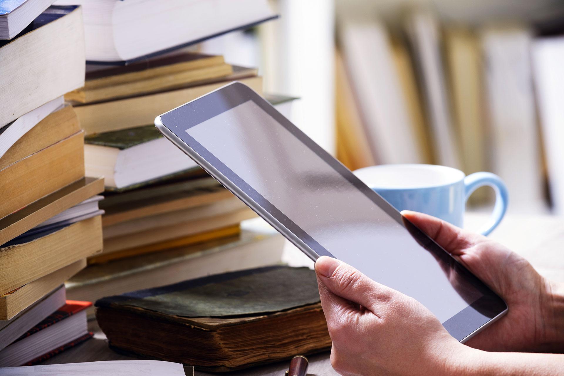człowiek patrzący na tablet, przed nim stos książek