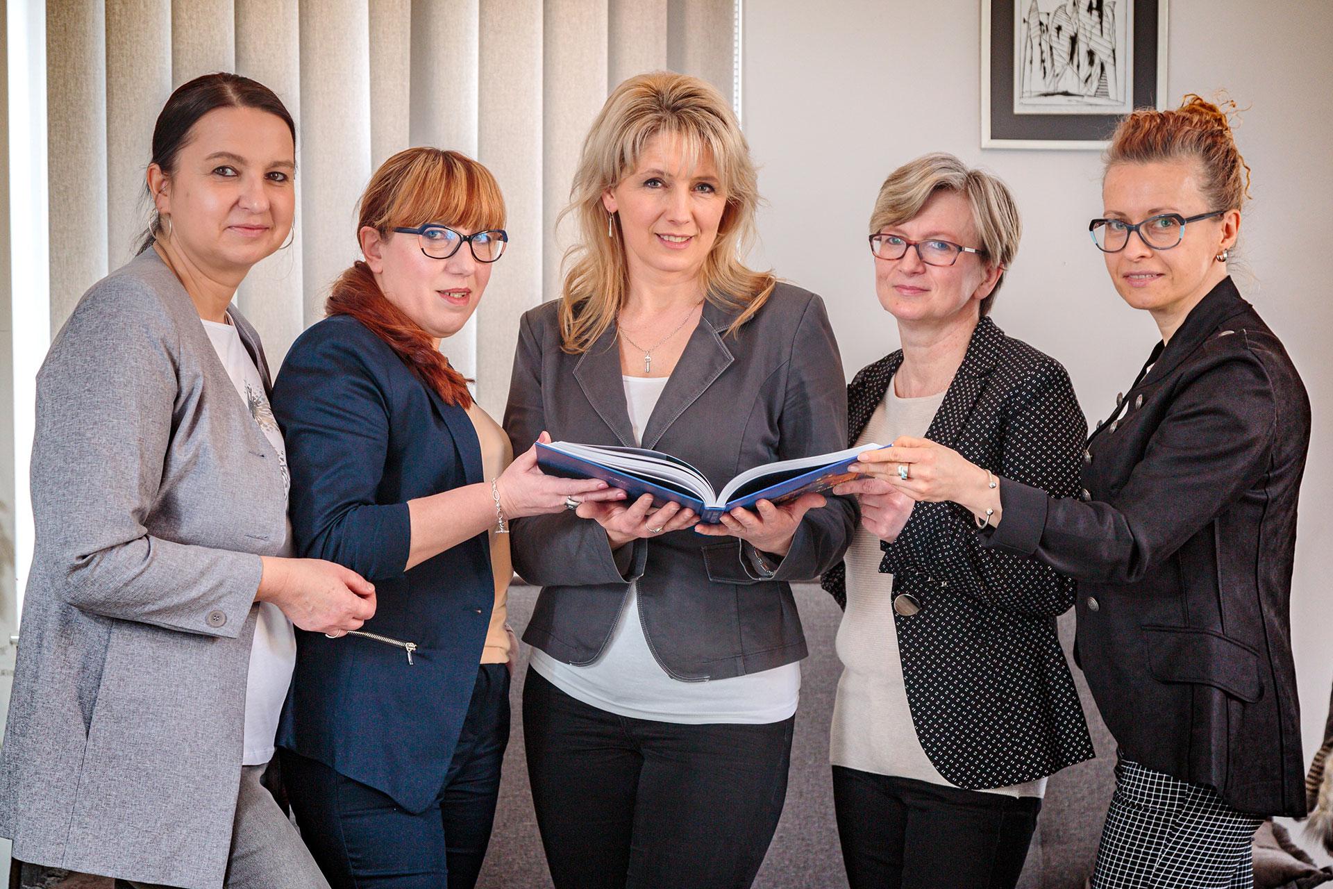stojące kobiety trzymające książkę - zespół Wydawnictwa Ad Rem